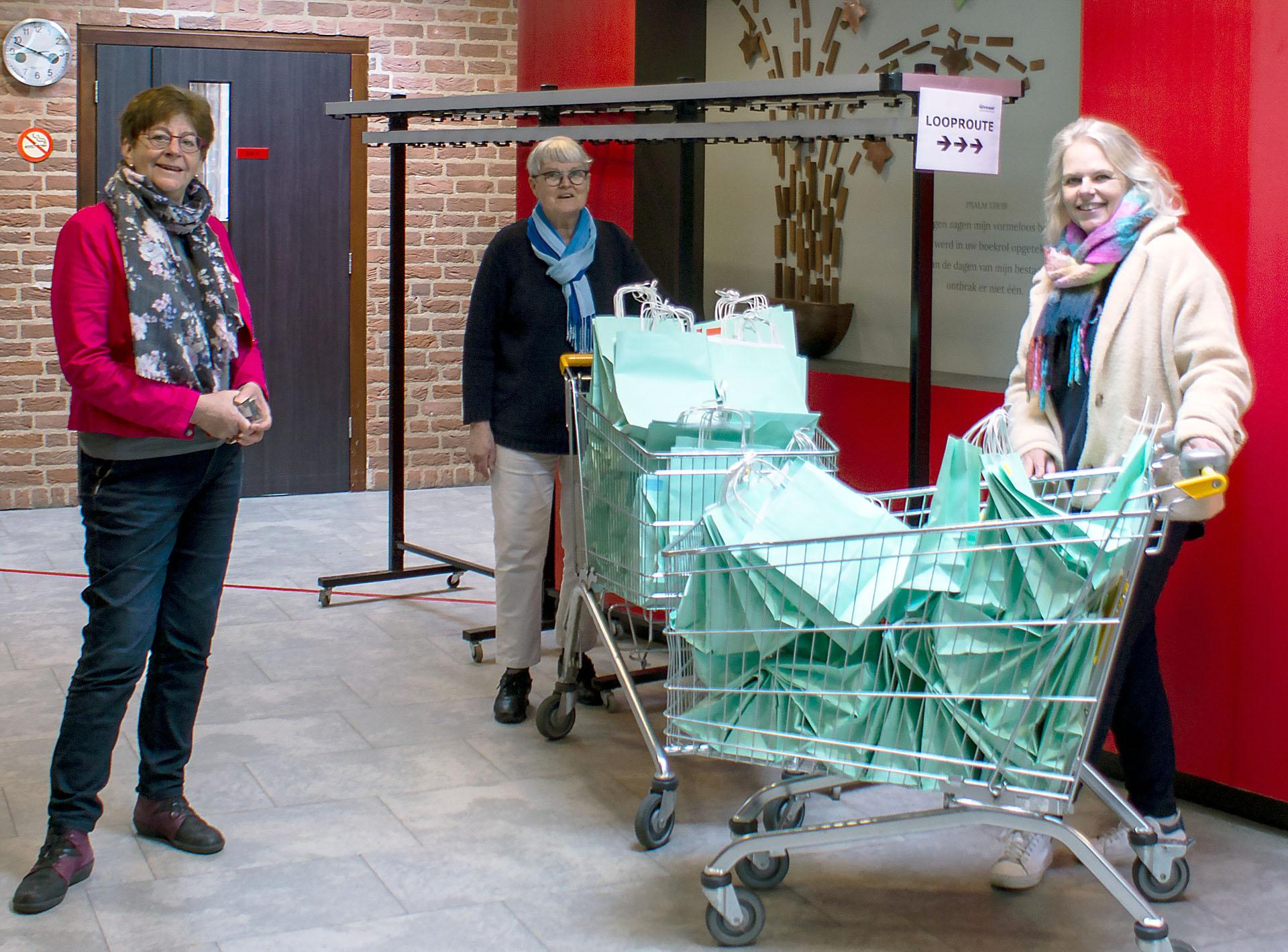 Tiny Pleiter (links) en Tetsje Feenstra nemen de poetspakketjes in ontvangst die Brigitte van der Linden (rechts) namens Mondzorg Leusden kwam overhandigen