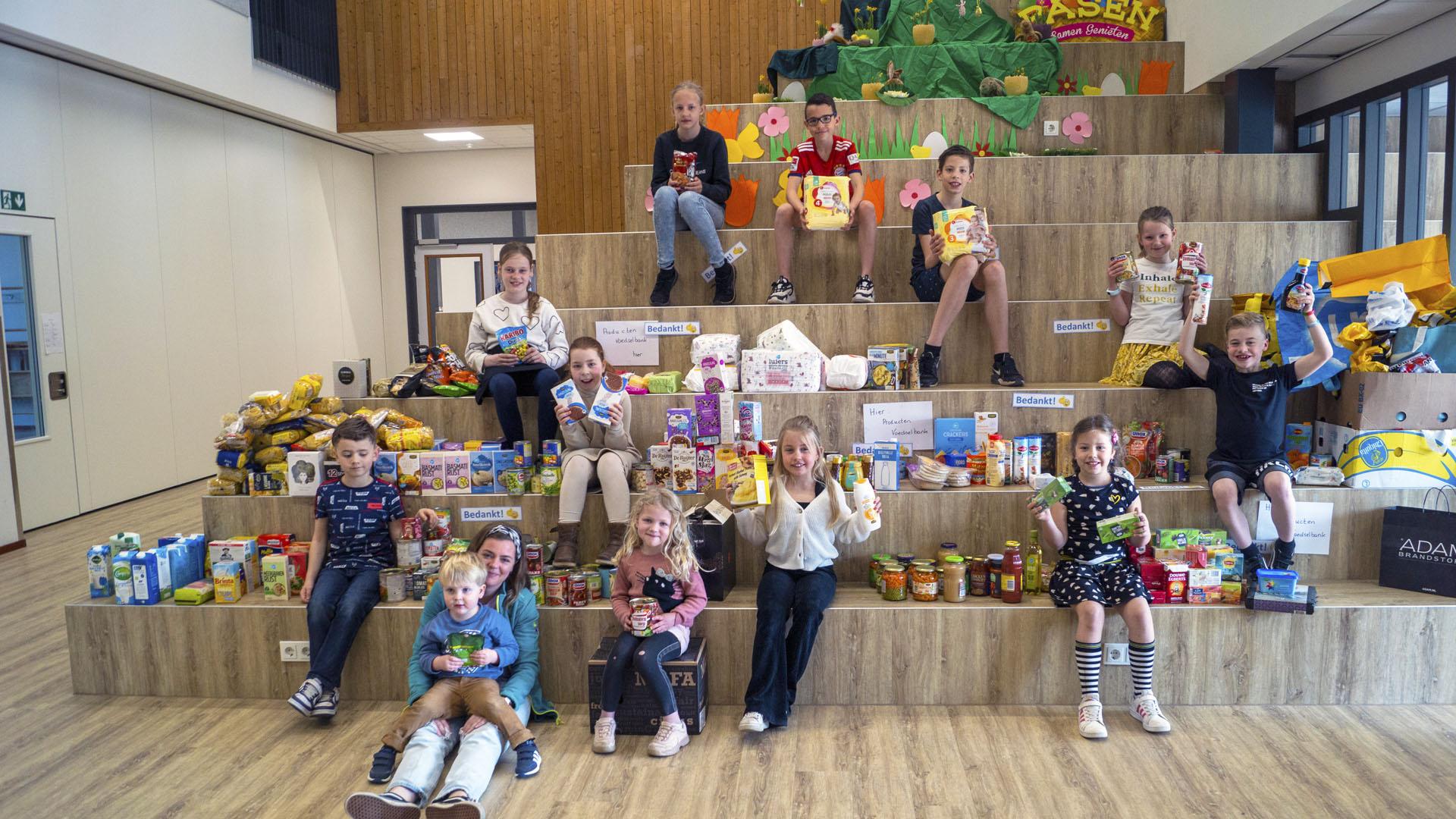 Enkele leerlingen van kindcentrum Berkelwijk poseren trots tussen een deel van de opbrengst van hun sociale collecte.